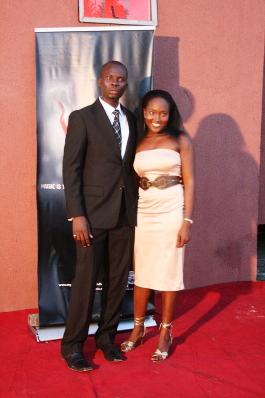 Mr. Omisore looks real surprised to find this pretty girl on his arm
